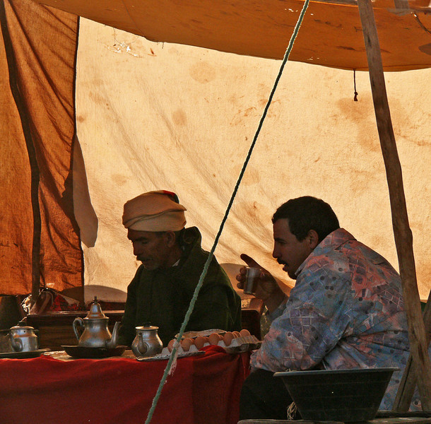 Tea Time, Attaouia Market - One of the largest markets in Morocco is held weekly in Attaouia, about an hour from Marrakesh. Everything from clothing to camels is sold and swapped here. I made this image of two fellows talking business in a tent over a cup of tea in the heart of the market.