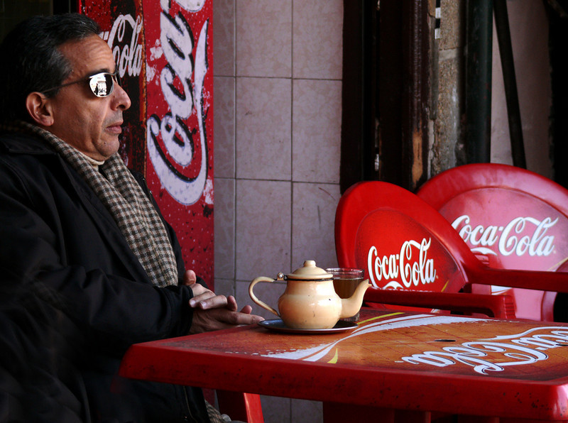 Tea Drinker, Marrakesh - A Marrakesh cafe patron savors his tea while engulfed in Coca Cola signage he never seemed to notice.