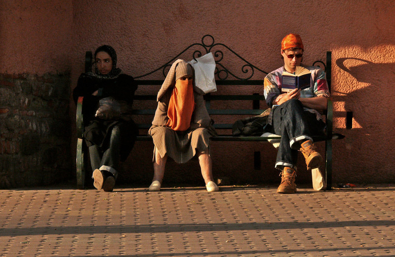 Strangers on a bench, Marrakesh - Seventy per cent of Marrakesh's population earns a living from tourism. It is always high-season in Marrakesh, the most popular destination in Morocco. Its benches are occupied day and night by a variety of visitors such as these.