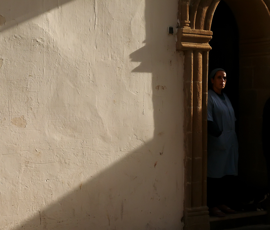 In the shadows, Essaouira - Nearly concealed in the shadows, an Essaouiran woman begins her day chatting with neighbors from her doorstep.