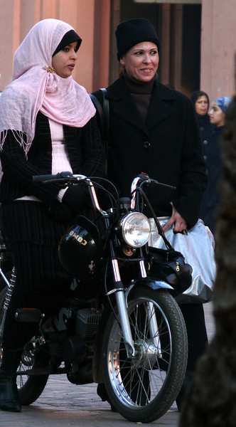 Motorized commuter, Marrakesh - With her head covered by a scarf instead of a helmet, this Marrakesh commuter enjoys her own transportation to and from the job.
