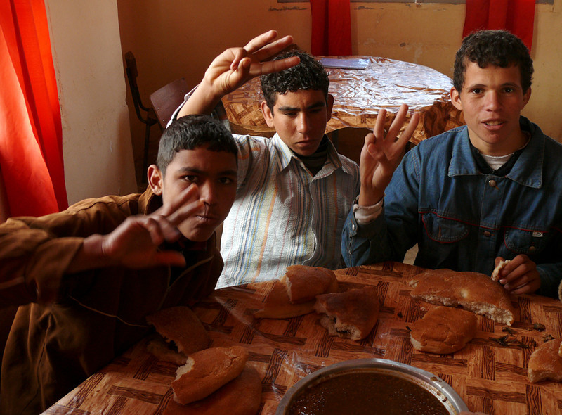 "Luncheon Salute, Tineghir - The boys of Dar ET-Tab, a boarding home for impovershed students, offer a luncheon salute of three fingers, summing up their school motto: ""Earth, Humanity, and Freedom."""