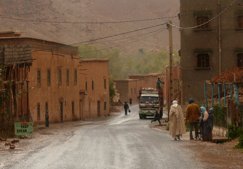 Street scene, Ait-Ali - Ait-Ali is a small village near the end of the Dades Gorge. The people who walk this road are going about their daily lives. A man tosses a package from a parked truck. A child runs in front of it. Shoppers come and go. The buildings look as if they have been here for a long time.