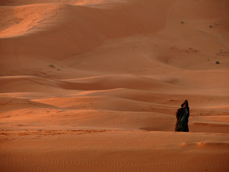 Berber at dawn, Erg Chebbi - A Saharan Berber walks the golden dunes of Erg Chebbi, just outside of our slumbering camp.