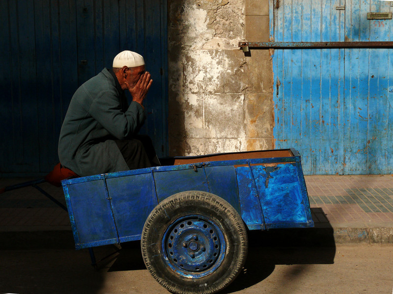 Man in blue cart, Essaouira - I saw this man sitting in a blue cart next to a blue door, lifting his hands to his face as if in prayer. Or perhaps he was just thinking. We will never know, and that is the mystery of this photograph.