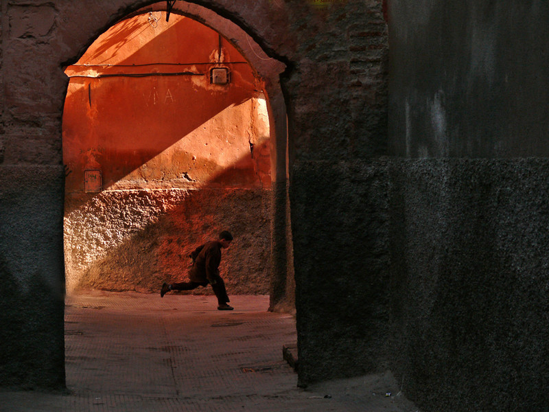Decisive moment, Marrakesh - This is a very special photograph, a spontaneous moment of pleasure caught in a very Moroccan environment. I was walking through the souks of Marrakesh when I saw a shaft of sunlight illuminating an ancient wall within an archway at the end of a dark and narrow street. I heard the distant voices of children at play, getting closer and closer. I framed the shot and waited, and within a few seconds a kid came flying into the arch. I squeezed the shutter button and caught him just as he landed. The magic of photography will always keep him in this spot, framed in fiery red, a symbol of youthful exuberance. This image offers fitting closure to this exotic and fascinating photographic journey through Morocco.