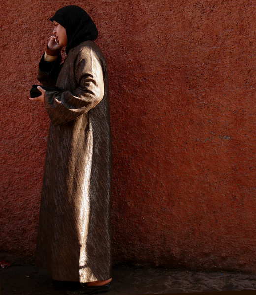Sliver of light, Marrakesh - She stands before a wall in Marrakesh's old walled city, a study in contrasts. A sliver of morning light slips between two buildings to illuminate just the edge of her garment. The rough texture of her clothing echoes the heavily textured wall behind her. Without the cell phone, this photo could have been made a century ago, with very few differences.