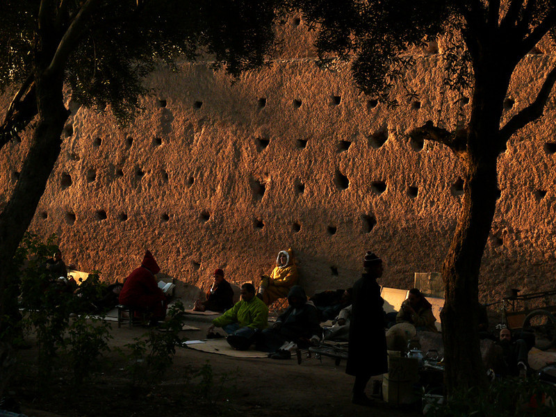 The walls of Old Marrakesh - The wall that completely encircles the medina of Marrakesh is 900 years old and stretches for 12 miles. I found this group of men resting and reading at the base of this wall as dusk approached.