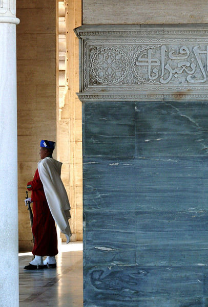 Sentry, Royal Tomb, Rabat - The four marble doorways of King Mohammed V's tomb are fronted by slender columns of Carrara marble, and songs of holy praise carved in Maghrebi script. A caped sentry stands guard over each entrance.
