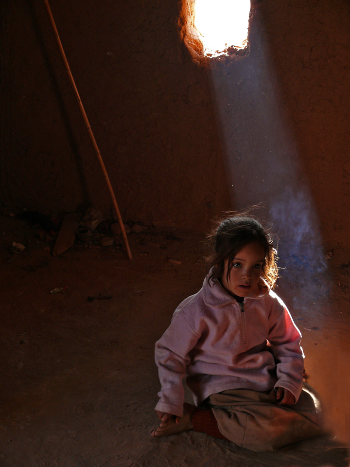 Semi-nomadic child, Sahara Desert - I photographed this little girl on the floor of her adobe hut, grazed by a shaft of light from its sole window. She watched with fascination as her mother served tea to us.
