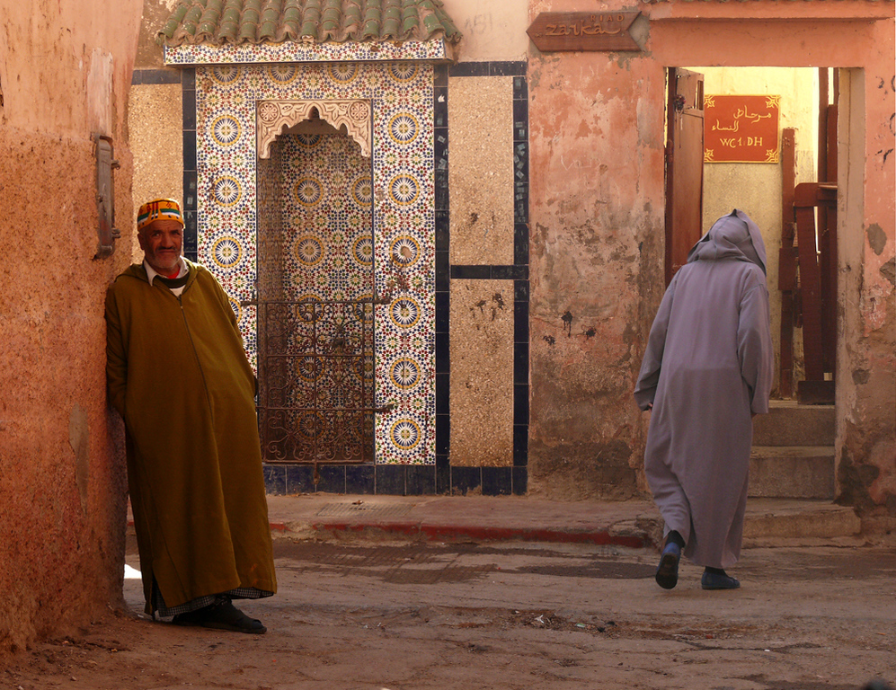 Two doors, Marrakesh - One door is elegantly tiled. The other is wide open -- leading to a public toilet. The man at left is the attendant, collecting about twelve cents from each and every visitor.