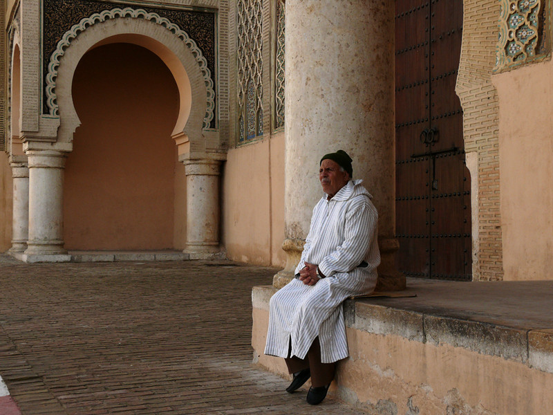 At the Bab Mansour, Meknes - The Bab Mansour (Gate of the Victorious Renegade) was designed by a Christian. It stands as a triumphal arch before the city. This man is using it for his own recreational purposes-- a bit of day dreaming, perhaps.