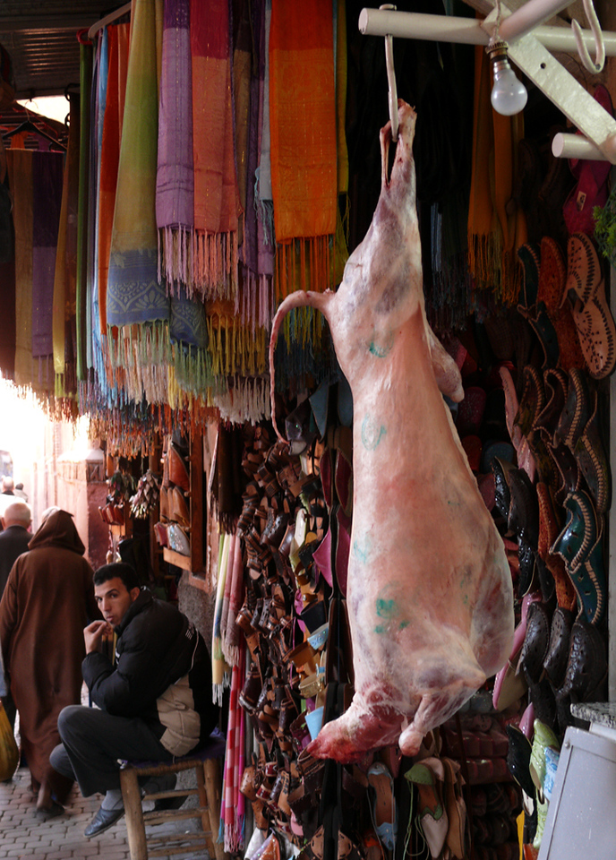 Goats, shoes, and scarves, Marrakesh - Freshly killed goats, racks of shoes and colorful scarfs are often found hanging side by side in the souks of Marrakesh.