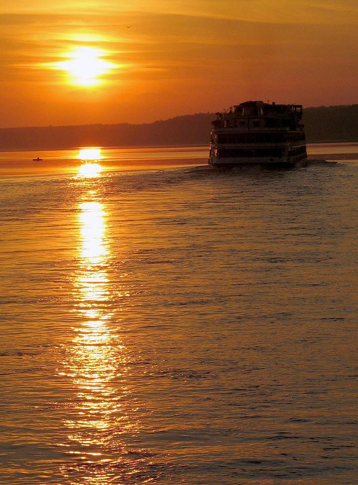 Sunset on the Volga - A cruise boat plows the waters of the Volga River, which has been chopped into a chain of vast reservoirs to supply the country with hydroelectricity.