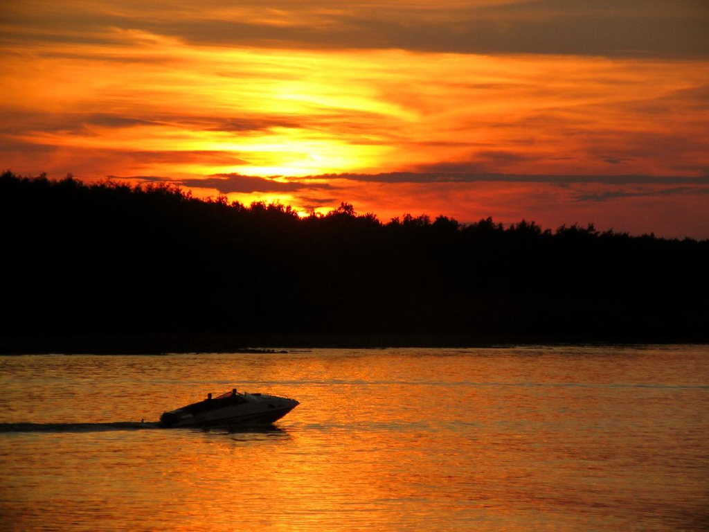 Fiery skies on the Volga - Under a blazing sunset, a motorboat cuts through the waters of the Volga near the provincial city of Jaroslavl.