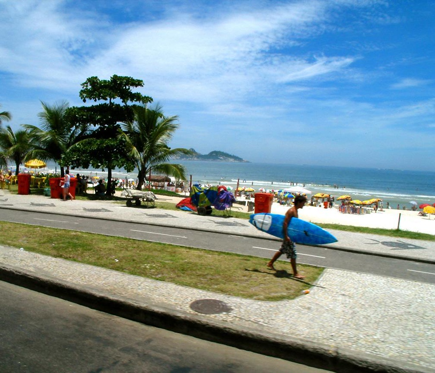 The surf beckons - Rio thrives on samba, soccer, and surfing. Here, a Carioca bearing a surfboard heads for some big waves.