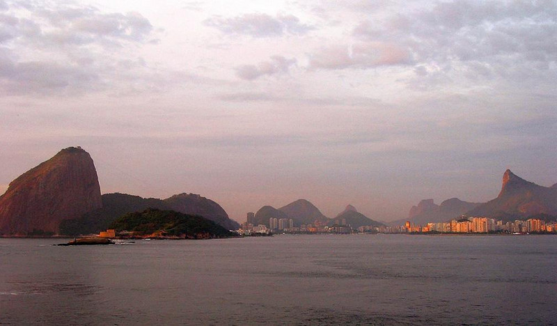 Rio at dawn: Sugar Loaf to Corcovado - A dawn arrival in Rio de Janeiro offers a panoramic view of one of the world's most spectacular city settings. Sugar Loaf rises at left, and Corcovado looms over the high rise buildings at right.