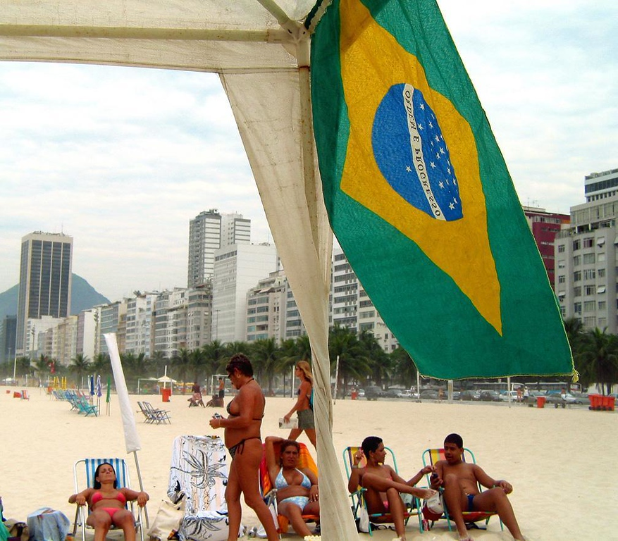 Waiting for the sun - Under a Brazilian flag, determined Cariocas try to catch some sun on Copacabana Beach, even on an overcast morning.