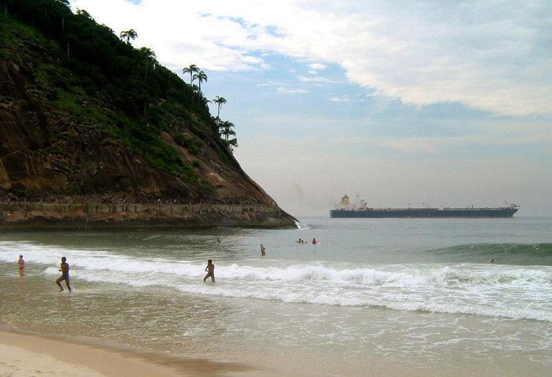 Freighter off Copacabana Beach - As swimmers enjoy Copacabana's surf, a huge freighter slips past the hill marking one end of the famed beach.