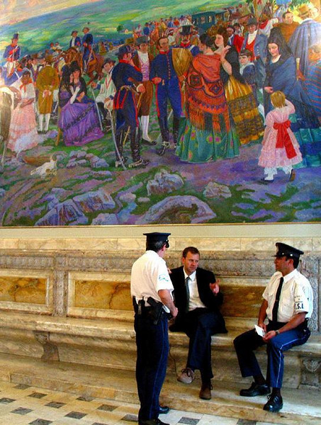Security conference - Under a colorful mural depicting the country's struggle for independence, two security guards are briefed in the lobby of Uruguay's Congress Building.
