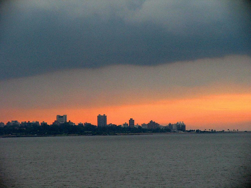Stormy dawn on the Rio de la Plata - A rising sun proved no match for the layers of rainclouds that massed over Montevideo, Uruguay, as we entered its harbor on the Rio de la Plata. The sediment-laden waters of the Rio de la Plata form the boundary between Uruguay and Argentina, 57 miles wide at Montevideo.