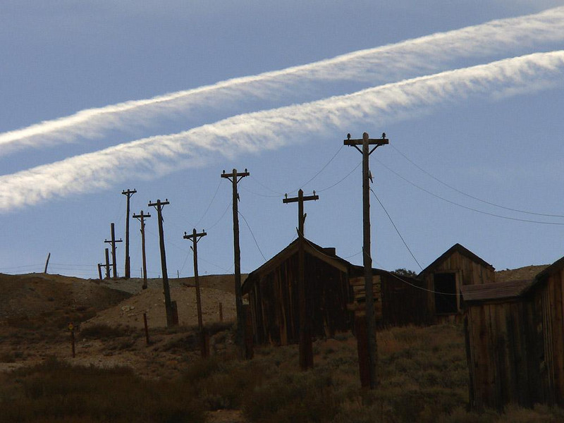 Contrails over Bodie - Past and present collide in this image of Bodies east end. 19th century utility poles point skyward at contrails left by 21st century jet aircraft.