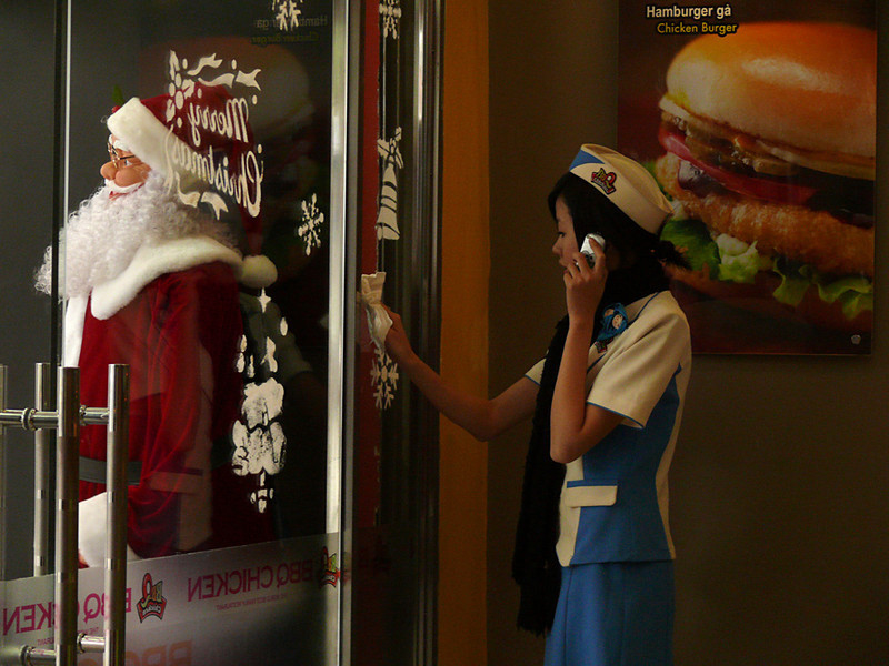 Multi-tasking, Hanoi - A fast-food worker chats on her cell phone while cleaning her restaurant's front door. She is squeezed between reminders of her job -- a huge hamburger -- and the holiday enticement that stands just beyond the glass.