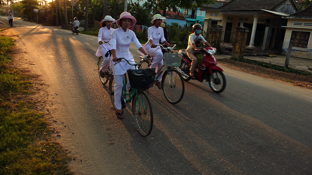 Homeward bound, Hoi An - High School girls in Vietnam wear distinctive uniforms. In Hoi An, they are dressed all in white. This group was on the way home as the sun set on Christmas eve.