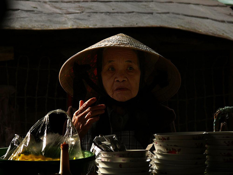 Breakfast at the market, Dalat - This woman was enjoying a bowl of soup for breakfast while I made her picture. She saw me, but her mind seemed elsewhere.