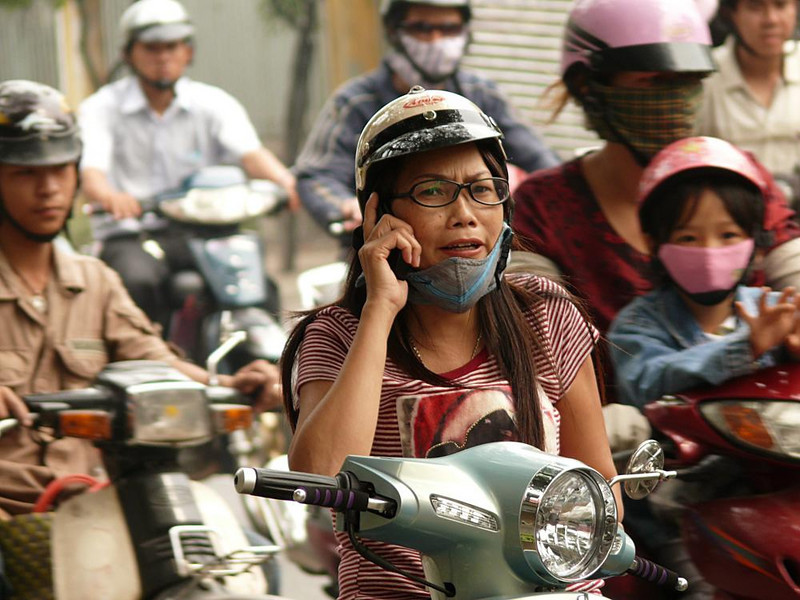 Cell phone on a motorbike, Saigon - Saigon, the largest city in Vietnam, is home to eight million people. Most of them seem to ride motorbikes. This woman is trying to make a call over the din of revving engines at a stop light.