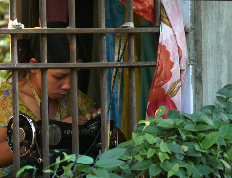 Tied to her job, Hoi An - It was the tape measure that drew my eye. It hangs around her neck and around the bars that guard her window. While much of the world celebrated Christmas eve, her work was her priority.