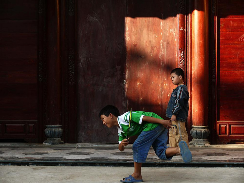 Street game, Hoi An - I loved the energy this young boy puts into his volley on the historic streets of Hoi An. The child just behind him seems to stand in awe of his prowess.