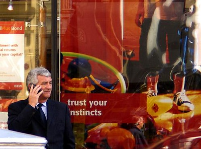 Dealing in Dublin - A Dubliner does business on O'Connell Street. I thought the ad in the window behind him provided an appropriate context.