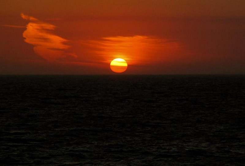 Sunset off Falmouth - I've seldom seen a setting sun as beautiful as this one. The wisps of clouds that embrace it seem reluctant to watch it slip below the horizon.