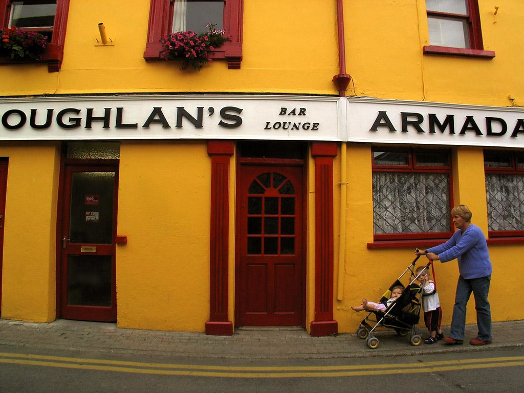 Double Take in Kinsale - I liked the dark mustard color of this Kinsale building, and waited for someone to walk past it. I got my wish when a mother and her young son appeared, both pushing the stroller of a younger family member.