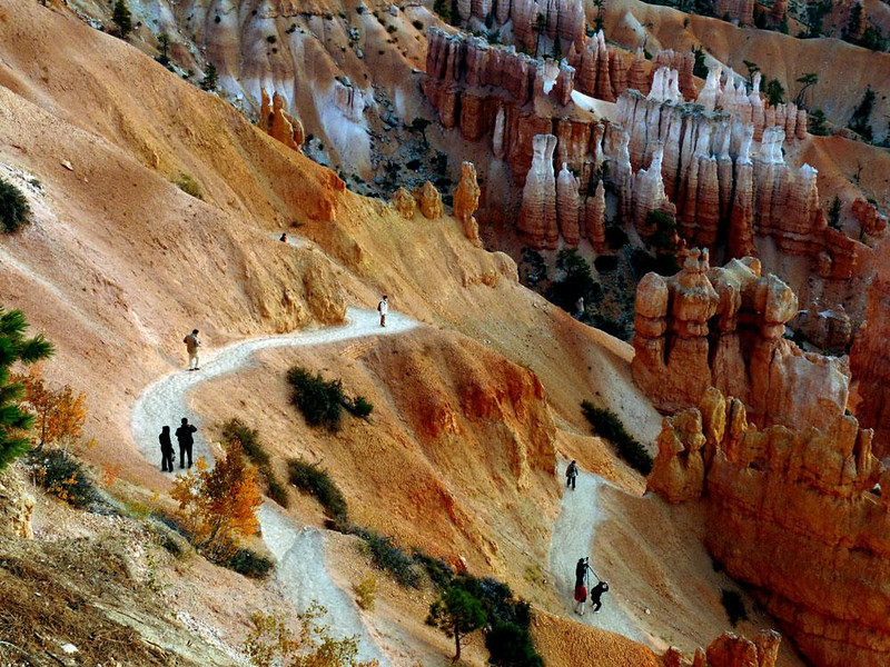 Tourist Trail, Bryce Canyon - Bryce, like most National Parks, is designed for tourists. I incorporate nine of them into this image as they walk the trails and photograph the ancient hoodoos from close vantage points. This image tells the story of both Bryce and those who come to marvel at its geological splendors. The colors are unlike anything, anywhere. The figures are tiny, incongruously dwarfed by their surroundings. They do the things tourists do at Bryce, hike, talk, shoot, and shoot some more.