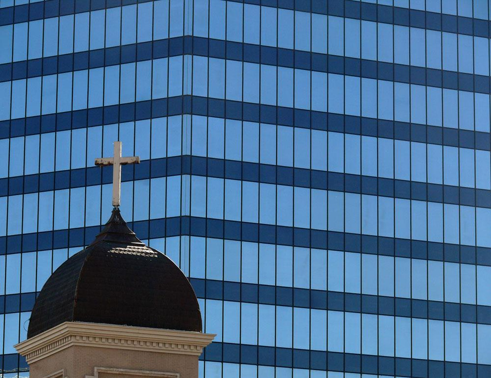 Old and new in Salt Lake City - I juxtapose a massive new downtown office building against the turret of an old neighborhood church to contrast spirituality to commerce and the old to the new. The glass windows of the office building, reflecting the deep blue Utah sky, seem opaque and blind to what is around them. They stare at the church like hundreds of blank eyes.
