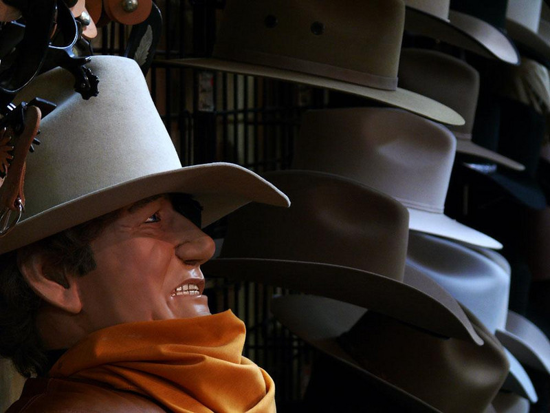 Stetsons for sale, Kanab, Utah - A life-sized mannequin of the late movie star John Wayne relaxes among the Stetsons in the hat department of the largest tourist shop in Kanab.