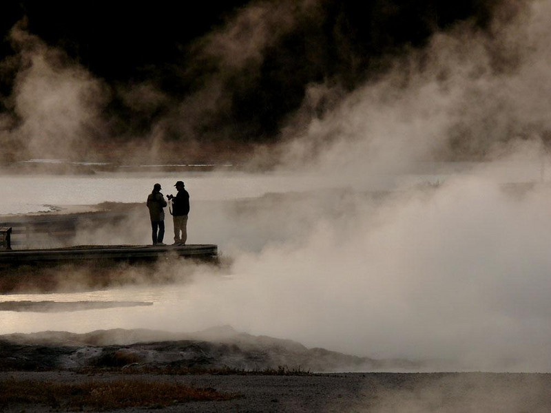 Hot Lake, Yellowstone - Hot Lake, fed by thermal springs, lives up its simple name. When the evening chill arrives, clouds of steam envelope visitors, including this couple, who seem to be trying to figure out how to photograph what they are seeing. For me, this scene was magical, but without the people, it would be meaningless.