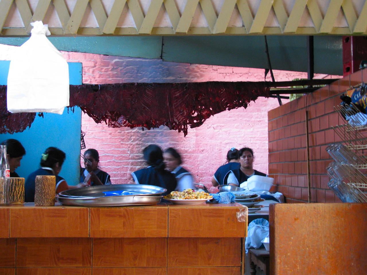 En la Picanteria 'La Chayo', la cocina super movida, con los trozos de carne secandose...<br /> <br /> At the Picaneria 'La Chayo', the kitchen is buzzling with orders, while the meat is being dried above...
