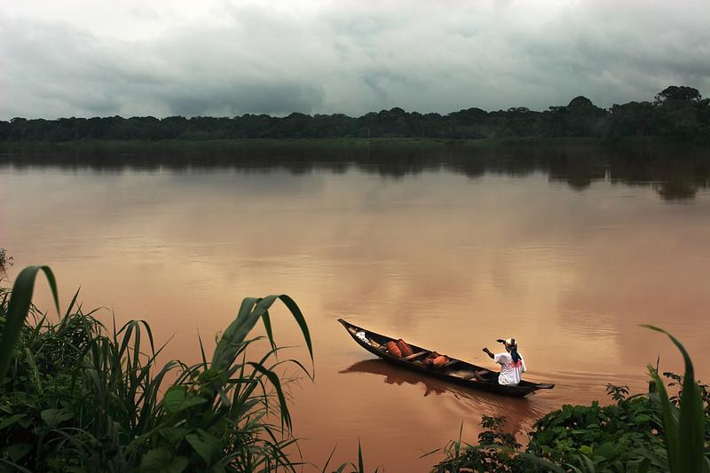Woman padding along the Sanaga river during the rainy season, Littoral, Cameroon.