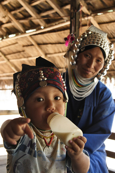 An Akha family in the hills of the Golden triangle, Myanmar. All Akha women usually wear that hat since they believe their soul could be stolen if not protected by that huge metallic helmet.