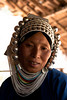 An Akha woman in the hills of the Golden triangle, Myanmar. All Akha women usually wear that hat since they believe their soul could be stolen if not protected by that huge metallic helmet.