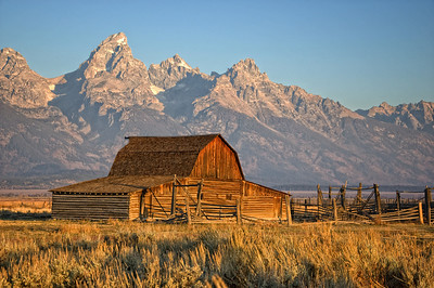 """Grand Teton Sunrise""  Our first day in Jackson, Wyoming we left the hotel at 630 am to get some sunrise shots.  It was cold and dark waiting for the sun to appear first on the mountains and then on this barn.  There was some light smoke in the air from area controlled burns.  From Wikipedia, the free encyclopedia Mormon Row Historic District Mormon Row is a line of homestead complexes along the Jackson-Moran Road near the southeast corner of Grand Teton National Park. The rural historic landscape's period of significance includes the construction of the Andy Chambers, T.A. Moulton and John Moulton farms from 1908 to the 1950's. Six building clusters and a separate ruin illustrate Mormon settlement in the area and comprise such features as drainage systems, barns, fields and corrals. The district occupies a spectacular site in Jackson Hole with the Teton Range rising in the background."
