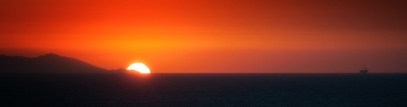 In this photo, the sun sets over the northern edge California's Catalina Island that is twenty-six miles away.  A cargo ship is also captured in this image.  The photo was shot from Newport Coast, California.