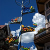 "Maypole""<br /> <br /> This Maypole was photgraphed at Lionshead Village in Vail, Colorado. Many variations of Maypoles are usually seen in real European villages.<br /> <br /> From Wikipedia, the free encyclopedia<br /> The maypole is a tall wooden pole (traditionally of maple (Acer), hawthorn or birch) erected to celebrate May Day or Midsummer. It may be a semi-permanent feature, standing in position year-round until it has to be repainted or replaced, or it may be a shorter, temporary structure. It may be decorated with several long coloured ribbons suspended from the top, festooned with flowers, draped in greenery, hung with large circular wreaths, or adorned with other symbols or decorations, depending on local and regional variances.<br /> With roots in Germanic paganism, the maypole traditionally appears in most Germanic countries, Germanic country-bordering and countries invaded by Germanic tribes after the fall of the Roman Empire (such as Spain, France and Italy), but most popularly in Germany, Sweden, Austria, England, the Czech Republic, Hungary, Slovakia, Slovenia, and Finland in modern times for spring, May Day, Beltane, and Midsummer festivities and rites.<br /> What is often thought of as the ""traditional"" English maypole (a somewhat shorter, plainer version of the Scandinavian pole with ribbons tied at the top and hanging to the ground) is a relatively recent development of the tradition, probably derived from the picturesque, Italianate dances performed in mid-19th century theatricals. It is usually this shorter, plainer maypole that people (usually school children) perform dances around, weaving the ribbons in and out to create striking patterns."