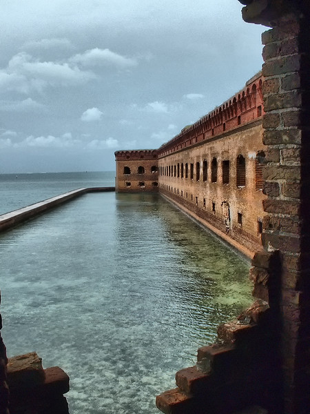"""""""Fort Jefferson Bastion""""<br /> <br /> <br /> From Wikipedia, the free encyclopedia<br /> """"During the Federal government shutdown of 1995, Dry Tortugas was closed along with all other national parks. Seeing this as having a damaging effect on their tourism-dependent economy, the residents Key West, Florida, raised money to keep Dry Tortugas open. The effort was inspired by the Smithsonian Institution, which raised private donations to keep its museums open during the shutdown.<br /> Failing to find anybody to accept the money to reopen the park, Key West residents, under the auspices of the satirical micronation Conch Republic, sent a flotilla of civilian boats and fire department boats to Fort Jefferson in order to reopen the national park. When officials attempted to enter the fort, they were cited. The citation was contested in court the following year, and the resultant case, The United States of America v. Peter Anderson, was quickly dropped.""""<br /> <br /> """"A bastion is a structure projecting outward from the main enclosure of a fortification, situated in both corners of a straight wall (termed curtain), facilitating active defense against assaulting troops. It allows the defenders of the fort to cover adjacent bastions and curtains with defensive fire.<br /> The bastion was designed to offer a full range on which to attack oncoming troops. Previous fortifications were of little use within a certain range. The bastion solved this problem. By using a cannon to cover the curtain side of the wall, the forward cannon could concentrate on oncoming targets."""""""