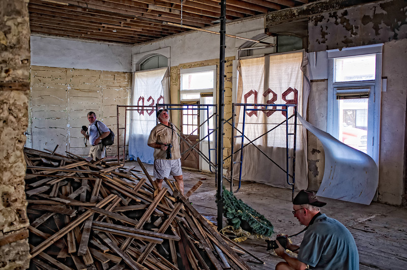 "July 18, 2011 - ""A Work In Process""<br /> <br /> Our ""Walk-About"" photo group starting the capture of the inside of the Granbury bank building in renovation.  The pile of original floorboards will be re-installed as construction progresses.  The remnant of a spiral staircase is not original to the building.  We reached the second floor by an outside staircase.<br /> <br /> Fellow Smuggers:  center, str8aero - on right, fireflystudio<br /> and not yet a Smugger on far left, Greg"
