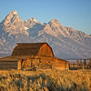 """""""Grand Teton Sunrise""""<br /> <br /> Our first day in Jackson, Wyoming we left the hotel at 630 am to get some sunrise shots.  It was cold and dark waiting for the sun to appear first on the mountains and then on this barn.  There was some light smoke in the air from area controlled burns.<br /> <br /> From Wikipedia, the free encyclopedia<br /> Mormon Row Historic District<br /> Mormon Row is a line of homestead complexes along the Jackson-Moran Road near the southeast corner of Grand Teton National Park. The rural historic landscape's period of significance includes the construction of the Andy Chambers, T.A. Moulton and John Moulton farms from 1908 to the 1950's. Six building clusters and a separate ruin illustrate Mormon settlement in the area and comprise such features as drainage systems, barns, fields and corrals.<br /> The district occupies a spectacular site in Jackson Hole with the Teton Range rising in the background."""
