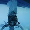 Shelda walking upside down under the dive boat!